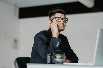 Young photographer working with laptop in office and talking on phone