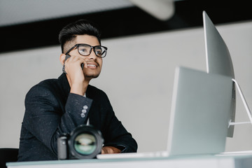 handsome young man retouching photos at workplace while use phone in office