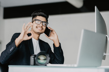 Young indian photographer with okay sign working with laptop in office and talking on phone