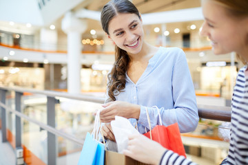 Young cheerful woman with bunch of paperbags looking at her friend while showing purchase