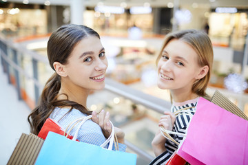 Two happy girls with bags looking at you while going to visit more department in the mall at season of sale