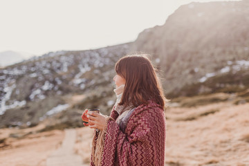 young woman enjoying nature in mountain covered with a blanket and a canteen. relax concept. sunny weather
