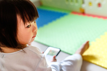 Asian little girl playing smartphone.