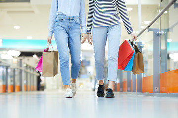 Young casual shoppers in pullovers and blue jeans moving down large modern mall and carrying bags with purchases