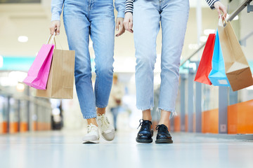 Legs of two young shopaholics in casualwear visiting modern mall at season of xmas sale
