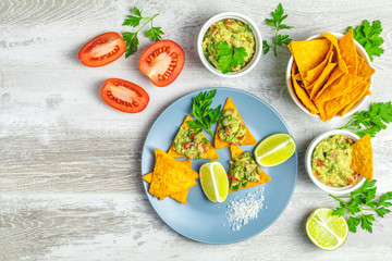 Guacamole and nachos with ingredients on the background of a light gray wooden board.