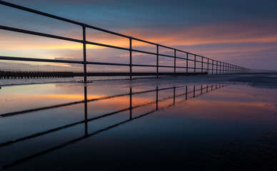 Safety railings reflecting in a puddle at sunrise on Swansea's West Pier with the East Pier in the background, Wales, UK