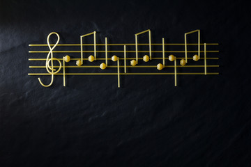 Musical Christmas sheet music paste isolated on a black textural background.