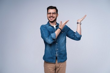 smiling young casual man presenting something on gray background.