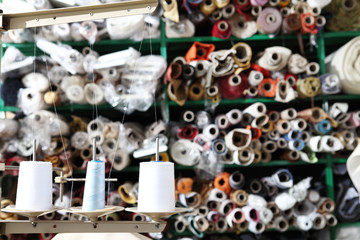 shelves with rolls of colored fabrics and spools of sewing thread in the foreground