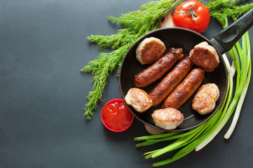 meat cutlets, sausages, tomato and tomato sauce, greens and green onion on black background with copy space, domestic food or domestic cooking concept