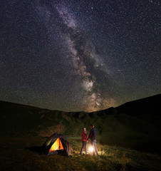 Young man and woman hikers holding hands, looking at each other, between them burning campfire near the illuminated tent under night starry sky with Milky way. Romantic night camping in the mountains