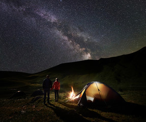 Back view of male and female backpackers holding hands, enjoying milky way on the starry sky at night camping. Beside illuminated tent and campfire is burning. Unusual landscape of mountains and lake