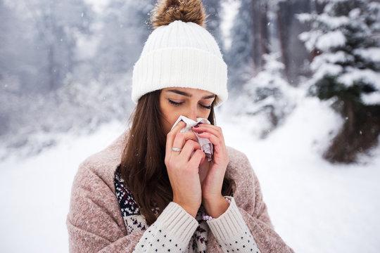 Portrait of sick woman using handkerchief at winter day