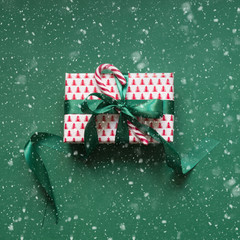 Christmas giftbox with candy cane on green surface. Xmas card. Top view.