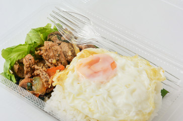 jasmine rice with spicy pork fried with thai pepper and fried egg in a transparent plastic box package, ready to eat