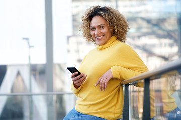 beautiful african american woman smiling with cellphone Fototapete