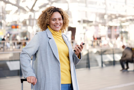happy african american woman in her 30s smiling with mobile phone at station