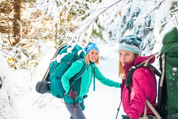 Two smiling women in a winter hike.