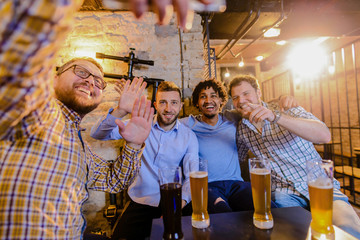 Four happy male friends having a picture of them while sitting in a bar and drinking beer.