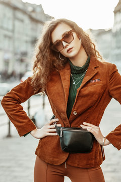Outdoor portrait of young confident fashionable woman wearing leopard print sunglasses, brown corduroy blazer, green turtleneck, black leather belt bag. Model posing in street of european city