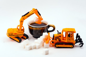 toy construction machines loads sugar into a real cup of coffee on a light background
