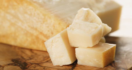 Closeup   of hard parmesan cheese cubes on olive cutting board