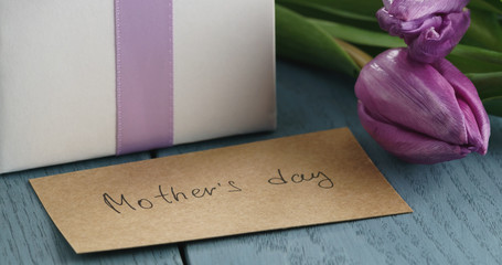 Closeup   of white gift box with purple bow and tulips on blue wood background