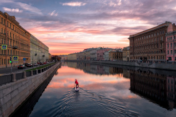 Lonely sup surfer moves along the Fontanka river at dawn