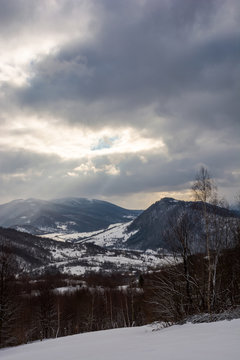 gloomy winter day in mountains. dark forest behind the snowy meadow. beam of light from grey cloudy sky fall into the distant valley