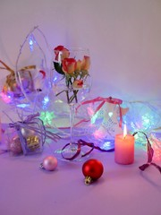 Decorative composition with Christmas decor, burning candle, rosebuds in a glass on a light background, seasonal winter holidays, home interior