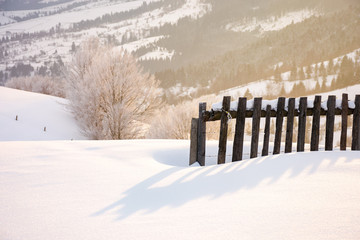 wooden fence in snow and morning sunlight. beautiful winter countryside background