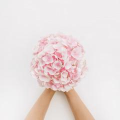 Fond de hotte en verre imprimé Hortensia Woman hands hold pink hydrangea flower bouquet on white background. Flat lay, top view floral concept.