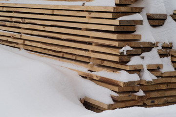 Woodpile stacked of firewood under the snow. Stack of cut wood under the snow.