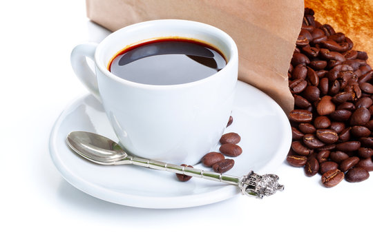 white cup of black coffee near the laying paper bag with coffee beans