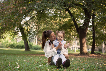 Mother and her baby daughter in park .