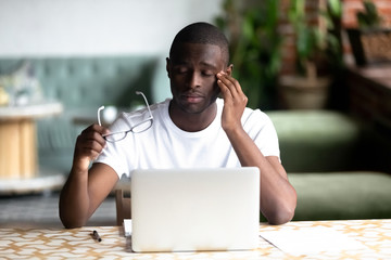 Tired African American man taking off glasses, feel eye strain after long work with laptop, computer, exhausted overworked student in cafe, sitting with closed eyes having bad sight vision problem