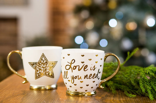 Two cups with text in Christmas interior with lights on background.