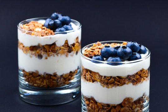 Homemade baked granola with yogurt and blueberries in a glass on a black background. Space for text or design.