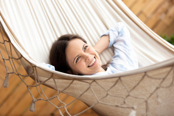 Happy smiling young woman lying in comfortable cozy hammock looking in distance, thinking about good things, successful future, calm girl stretching, dreaming, enjoying free time close up