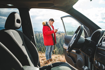 man standing near car with drone controller taking picture. view through car