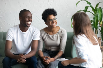 Happy African American couple at successful visit psychologist, smiling wife and husband sitting together on couch after good family therapy session, satisfied clients, help spouses solve problem
