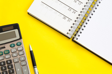 Accounting, financial concept, flat lay or top view of pen, calculator with white notepad, on vivid yellow background table with blank copy space,calendar, math, cost, tax or investment calculation.