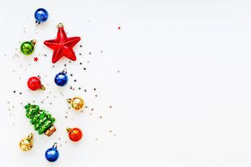 Christmas background with decorations. New Year symbol - fir tree. Shiny colorful balls, star and confetti. Flat lay, top view. Place for text.