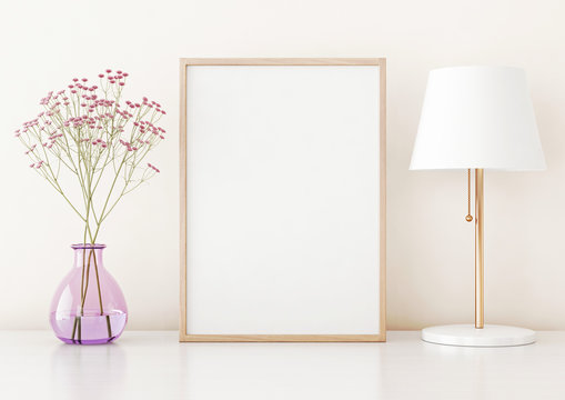 Home interior poster mock up with vertical frame on table, flowers in vase and lamp on warm white wall background. 3D rendering.