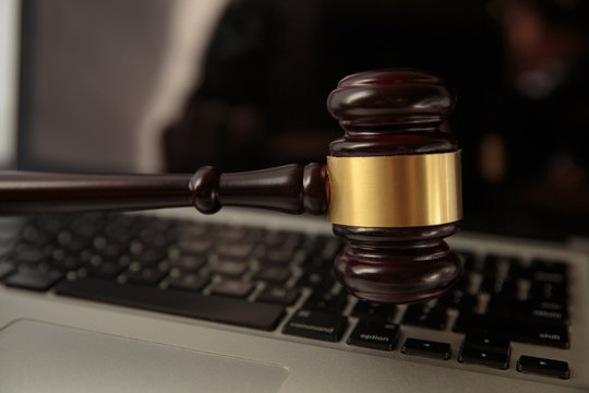 Online auction. Auction or judge gavel on a computer keyboard. 3d illustration.Close Up Of Wooden Brown Gavel On Laptop