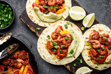 Fajitas in tortillas with fried shrimps, bell peppers and onion served up with avocado and green onions on wooden cutting board, top view, flat lay