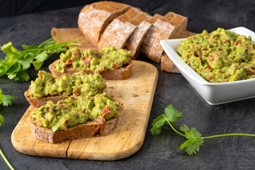 Fresh bread with Mexican homemade guacamole on a black table.
