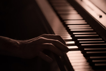 male hands on the piano keys closeup of a beautiful colorful background