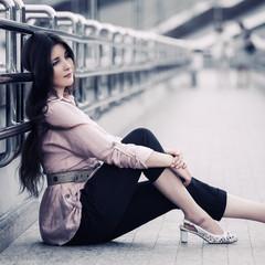 Sad young fashion woman sitting on the street sidewalk